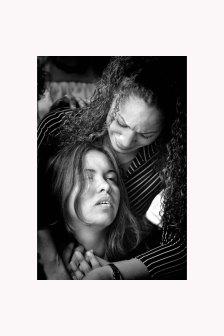 entierro1:Mientras los compañeros de armas completaban los rituales militares en honor a Kelvin Feliciano Guitérrez, su viuda Sharon Crespo Cordero busca consuelo en su cuñada Walesaka.